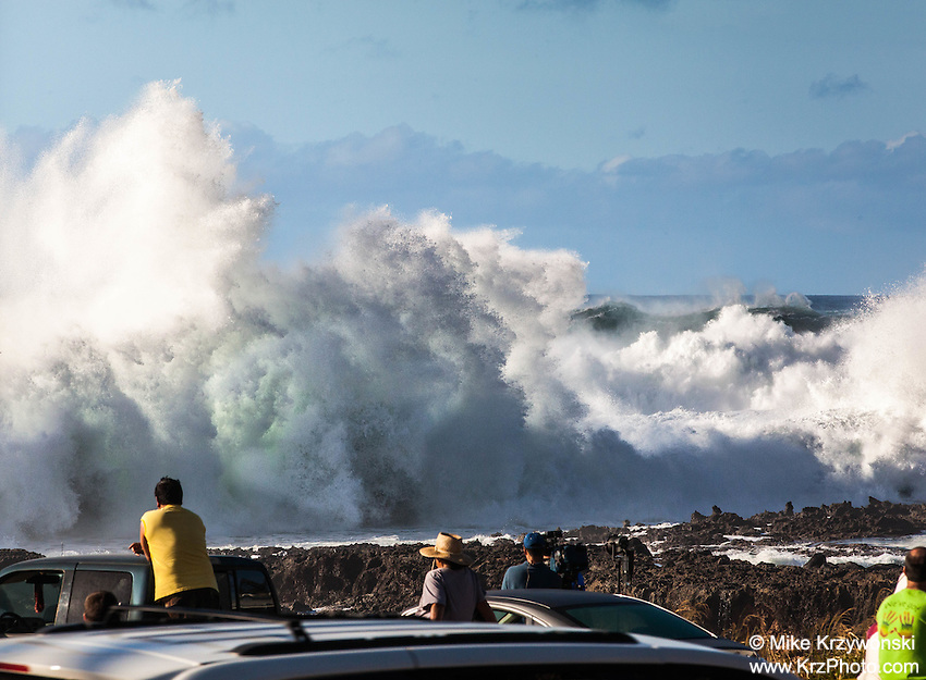 Spectators watching giant waves crashing against rocks during a large winter swell at Shark's Cove, North Shore, Oahu