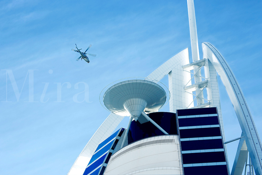 Guests arrive by helicopter at the Burj al Arab Hotel, an icon of Dubai built in the shape of the sail of a dhow, which stands on an artificial island just off Jumeirah Beach.   Dubai. United Arab Emirates.