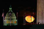A waning gibbous moon gets between the Capitol and the Washington Monument.
