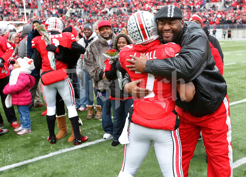 Ohio State Buckeyes running back Jordan Hall (7) greets his family during Senior Day celebration before the college football game between the Ohio State Buckeyes and the Indiana Hoosiers at Ohio Stadium in Columbus, Saturday afternoon, November 23, 2013. The Ohio State Buckeyes defeated the Indiana Hoosiers 42 - 14. (The Columbus Dispatch / Eamon Queeney)