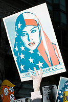 "A man holds a ""We the People"" poster depicting a Muslim woman wearing an American flag hijab near an entrypoint for the National Mall before the inauguration of President-elect Donald Trump on Jan. 20, 2017, in Washington, D.C."