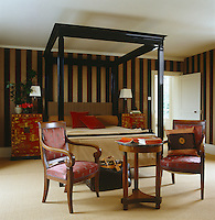A pair of Chinoiserie cabinets flanks a canopy bed designed by Todd Hase with a group of Biedermeier furniture in the foreground