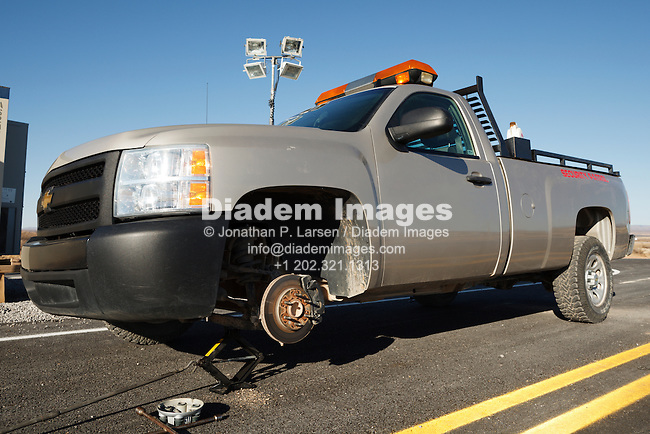 A pickup truck with a missing front wheel jacked up.
