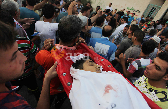Palestinian mourners carry the body of eleven-year-old Mohammed Eweda, who medics said was killed along with his five-year-old sister Amal in an Israeli military strike on their house, during their funeral in Rafah in the southern Gaza Strip on August 4, 2014. Israel insisted there will be no end to its bloody military campaign in Gaza without achieving long-term security for its people, shunning increasingly vocal world demands for a truce. Photo by Ashraf Amra