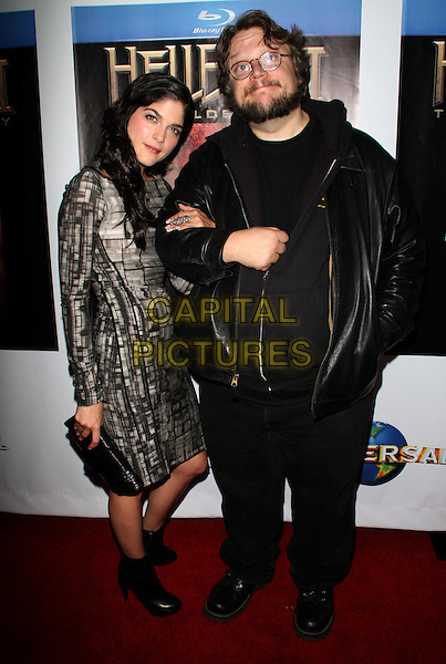 """SELMA BLAIR & GUILLERMO DEL TORO.""""Hellboy II The Golden Army """" DVD Blue-Ray Release Party held at Club Element, Hollywood, California, USA..November 11th, 2008.full length black ankle boots grey gray white pattern dress clutch bag leather jacket arms linked glasses trousers .CAP/ADM/FS.©Faye Sadou/AdMedia/Capital Pictures."""