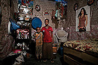 Fit Fit, 25 years old and her son Letmegaeta, 11 years old, portrayed in the shack where they live and where Fit Fit works as a commercial sex worker in the city of Bahir Dar, Northern Amhara region, on March 4, 2009. FIt Fit escaped from her husband to whom she was sold into marriage at the age of 7 years old. She was help by a relative who also escaped years before and came back to her village to rescue her. Fit Fit's son spends most his days with elderly women, former commercial sex workers who live nearby and who take care of the children while their mothers are working. The photo was taken on March 4, 2009...While in decline, early child marriage is still widely spread in rural areas of Ethiopia where families sell their daughters into marriage at ages as young as 5 years old...Names of subjects have been fictionalized and specific locations have been omitted to protect the identities of the children portrayed in the story.