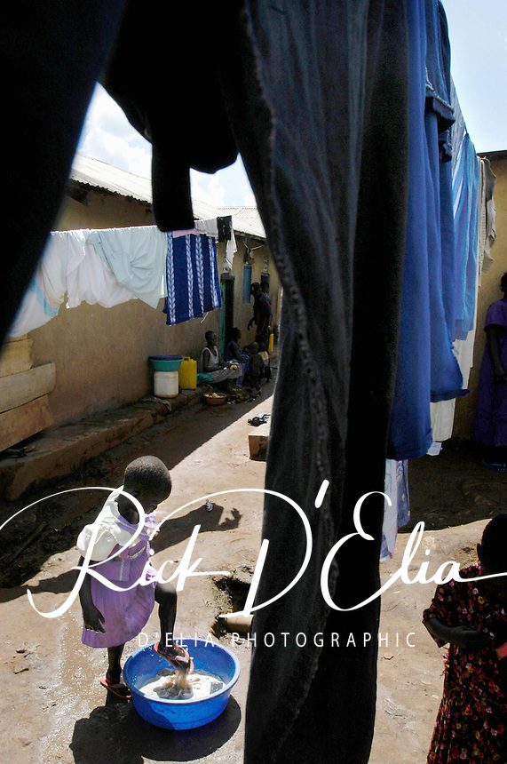 Ayoo Particia, 6,  washes her shoes after washing herself  in  among the drying laundry in the Soweto, section of Kampala Uganda  November 12, 2003. (Rick D'Elia)