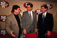 SANTA CLARA, CA: New San Francisco 49ers head football coach Steve Mariucci (center) is introduced to the media at a press conference in Santa Clara, CA in 1996 with owner Eddie DeBartolo (left) and president Carmen Policy. Photo by Brad Mangin.