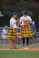 Savannah Bananas head coach Tyler Gillum (1) talks with Bill Knight (4) during a Coastal Plain League game against the Macon Bacon on July 15, 2020 at Grayson Stadium in Savannah, Georgia.  Savannah wore kilts for their St. Patrick's Day in July promotion.  (Mike Janes/Four Seam Images)