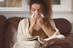 Young woman got sick, blowing her runny nose in a paper tissue, staying at home with a book