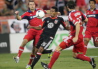 WASHINGTON, DC. - AUGUST 22, 2012:  Lionard Pajoy (26) of DC United cuts past  Austin Berry (22) and  Arnie Friedrich (23) of the Chicago Fire during an MLS match at RFK Stadium, in Washington DC,  on August 22. United won 4-2.