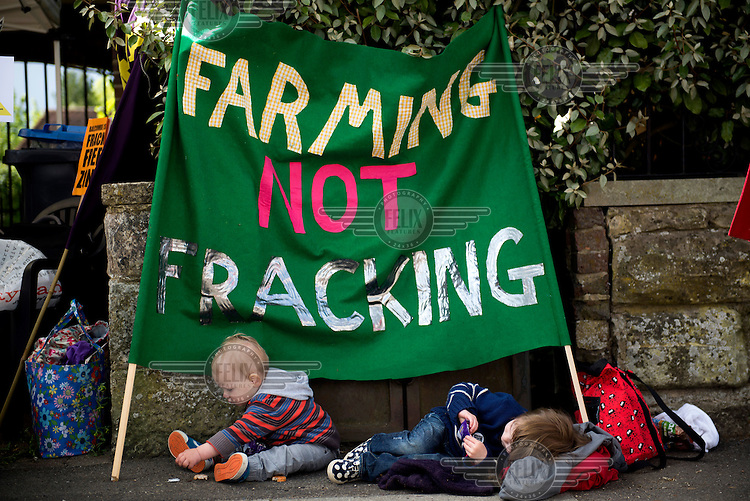 Toddlers rest beneath a banner during rally by residents of the West Sussex village of Balcombe to protest that Hydraulic Fracturing (fracking) company Cuadrilla Resources Ltd has been granted an exploration licence for a site close to the village. /Felix Features