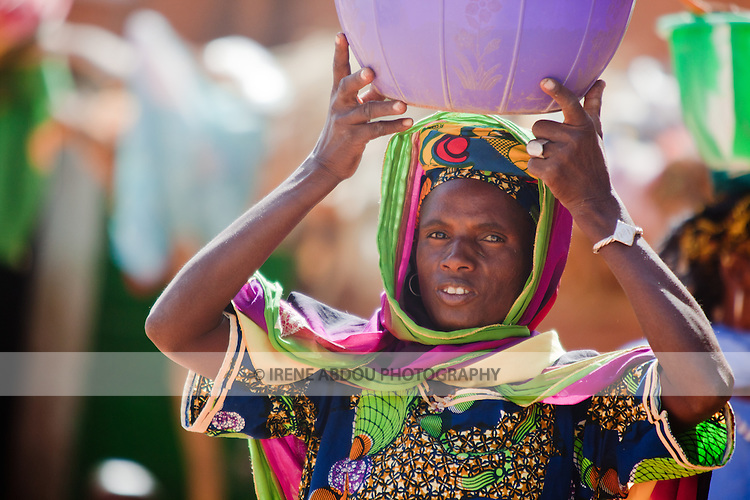 """In West Africa, certain villages have markets that """"assemble"""" at regular intervals, such as weekly or every three days.  People from villages around the region come on market day to buy and sell food, livestock, and other goods and services.  Here, a Fulani woman brings fresh milk to sell in the weekly Djibo market in northern Burkina Faso."""