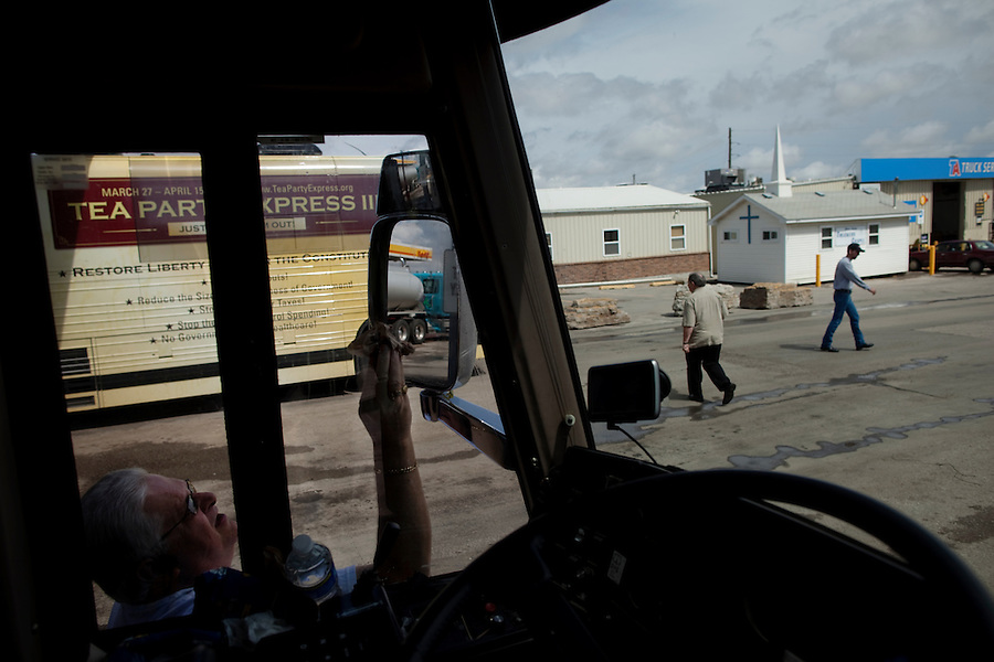 Highway 75 near Beto Junction, Kansas, April 2, 2010 - Tea Party Express bus driver Raymond March, left, cleans his mirrors during a gas stop en route to Tulsa, Oklahoma. The tour which began in Searchlight, NV, hometown of Senate Majority Leader Harry Reid, will wind through the 43 cities across the United States ending up in Washington, D.C. on April 15 for a tax day rally..