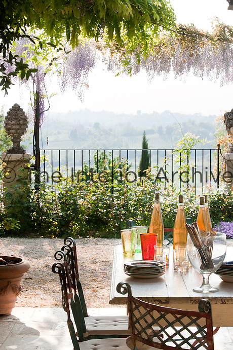 The terrace dining area is an idyllic spot for al fresco summer lunches with spectacular views past the wisteria of the rolling Italian countryside