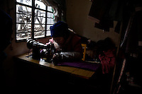 A tailor of the Hani ethnic minority sews traditional women's clothing in her shop in Sheng Cun Village, Yuanyang County, Yunnan Province, China.