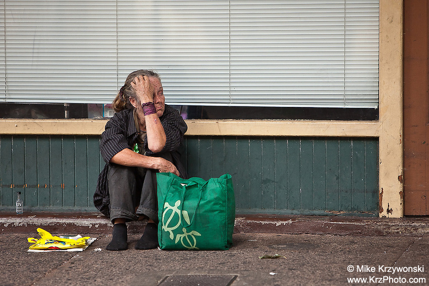 Homeless Caucasian woman sitting on sidewalk in Chinatown, Downtown Honolulu, Oahu, Hawaii