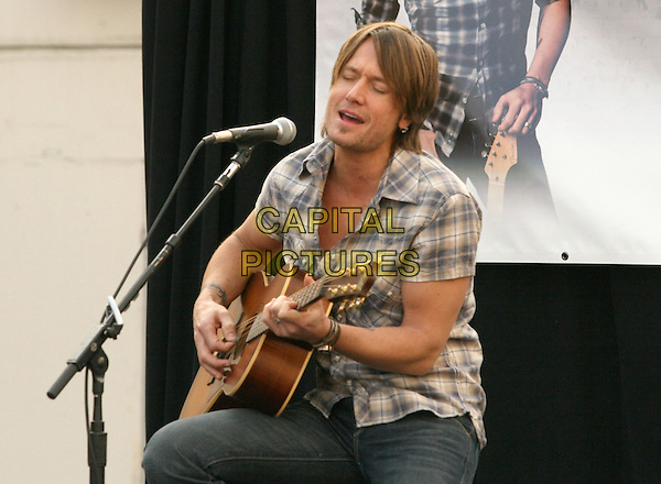 KEITH URBAN.is joined by Verizon Wireless and Samsung Mobile as he makes an in-store appearance for his fans at the Verizon Wireless store in Pasadena, California, USA, November 21st 2009                                                                   .half length music concert gig live on stage grey gray brown plaid checked check shirt jeans sitting microphone singing playing tattoo bracelets guitar .CAP/RKE/DVS.©DVS/RockinExposures/Capital Pictures