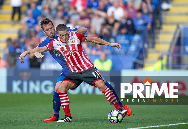 Dusan Tadic of Southampton told off Christian Fuchs of Leicester City during the Premier League match between Leicester City and Southampton at the King Power Stadium, Leicester, England on 2 October 2016. Photo by Andy Rowland.