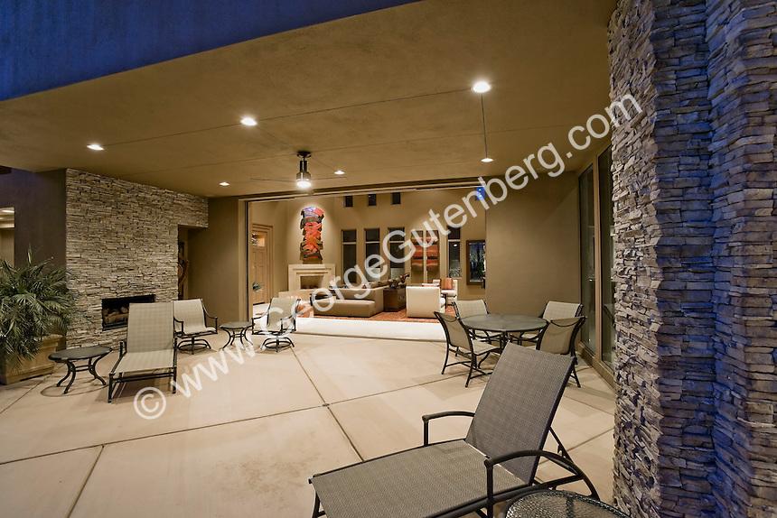 Outdoor patio area leads inside retractable pocket door of luxurious home