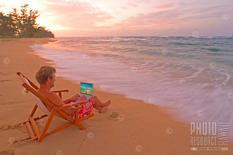 Surfing the web, man on tropical beach at sunset relaxing with computer, image of surfer