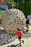 "Huntington, New York, U.S. 24th August 2013. A young boy has just stepped out from inside a rolling metal sculpture ""Sphere of Hope"" which his father is still in, at the art event ""Off the Walls"" Block Party, by SPARKBOOM, a Huntington Arts Council project created to help emerging artists, showcase talents, and help its artistic family network. The sculpture is by sculpture Steven Zaluski, and is created from human shapes welded together."