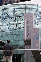 A man stands in front of a Chevrolet Volt advertisement pannel at the General Motors corporate headquarters in Detroit Renaissance Center Saturday June 8, 2013. General Motors Company, Inc., commonly known as GM  is an American multinational automotive corporation.