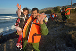 A refugee father and daughter wave after landing in an overcrowded rubber raft on a beach near Molyvos, on the Greek island of Lesbos, on October 30, 2015. They crossed the Aegean Sea from Turkey with other refugees and were received by local and international volunteers. They then proceeded on their way toward western Europe. The boat was provided by Turkish traffickers to whom the refugees paid huge sums to arrive in Greece.