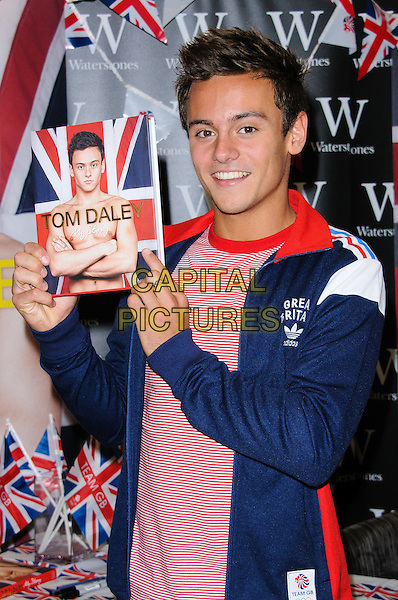 Tom Daley.Olympic medalist, Tom Daley signs copies of his autobiography 'My Story' at Bluewater shopping center, London, England..August 16th, 2012.half length blue jacket white red top book .CAP/CJ.©Chris Joseph/Capital Pictures.