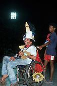 Rio de Janeiro, Brazil. Disabled man in a rusty old wheelchair with his carer having fun in his costume during carnival.