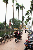VIETNAM, Hanoi, two people on a moped look for a place to park, Tran Quoc Pagoda