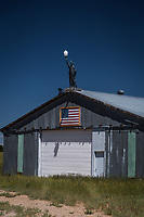 A Statue of Liberty replica sits on top of a metal outbuilding, visible from U.S. Route 40 east of Maybell, Colorado.