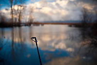 Fishing rod leans over the water at Hoover Reservoir on a cold fall day as the sun lights clouds on the eastern shoreline after a passing storm.
