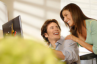 Lighthearted young couple at computer monitor.