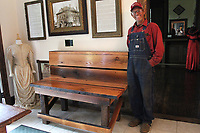 MEGAN DAVIS/MCDONALD COUNTY PRESS Jimmie Gideon stands next to a bench he built and donated to the McDonald County Historical Museum. The wood was reclaimed from the historic Puckett School in the county.
