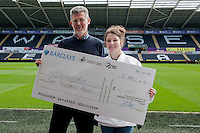 Friday 11 April 2014<br /> Pictured: Tony Clements of Swansea Harriers and Jade Lewis of Gendros Judo Club<br /> Re: Swansaid Cheque Presentation at the Liberty Stadium, Swansea Wales