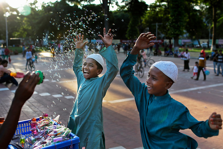 Bangladeshi students of an Islamic education school play with bubbles during a break in Dhaka, Bangladesh.
