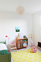 A sparsely furnished girl's bedroom with a green painted bed and yellow pattern rug.
