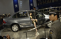 A security man guards while a model poses on a Peugeot 307 at the Auto China 2004 exhibition in Beijing, China..