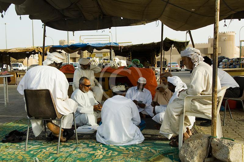 Oman, Buraimi, Omani men playing cards in marketplace