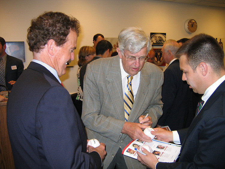 Former Washington Senator Mickey Vernon, a two-time batting champion, signs an autogrpah for Rep. Phil Gingrey (left) at a reception prior to the 44th Annual Roll Call Congressional Baseball Game.