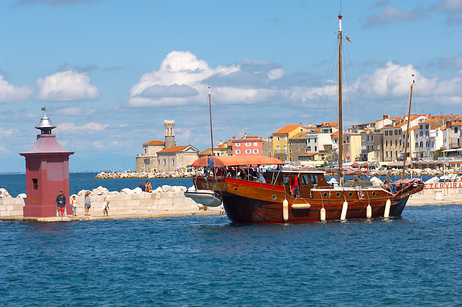 Harour entance with people relaxing and fishing off the harbour wall. Pirates ship.  Piran , Slovenia