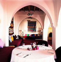 Burgundy-coloured rugs and banquettes scattered with colourful cushions furnish the dining room