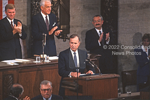 United States President George H.W. Bush speaks to a Joint Session of the U.S. Congress on the situation with Iraq and the Persian Gulf and on the federal deficit in the U.S. Capitol in Washington, D.C. on September 11, 1990.  Also pictured, from left, are U.S. Vice President Dan Quayle, Speaker of the U.S. House of Representatives Tom Foley (Democrat of Washington), and Clerk of the U.S. House Donnald K. Anderson.  At bottom is James T. Molloy, the 34th and last doorkeeper of the House of Representatives.<br /> Credit: Ron Sachs / CNP