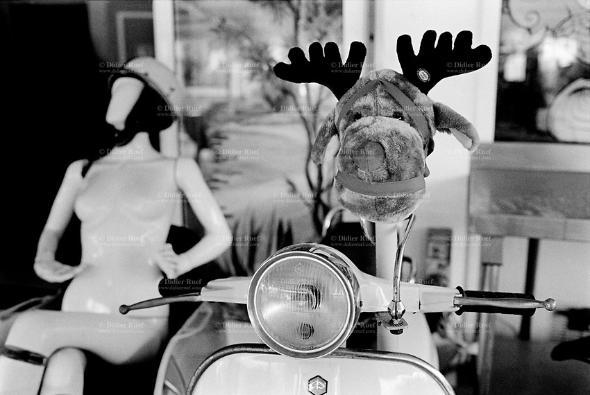 France. Alpes-Maritimes department. Restaurant. A Vespa scooter with a stuffed moose toy. A nakefd woman manikin with a motorbike helmet. Vespa is an Italian brand of scooter manufactured by Piaggio. A stuffed toy is a toy sewn from a textile, and stuffed with a soft material. In North American English they are variously referred to as plush toys, plushies, snuggies, stuffies, snuggled animals or stuffed animals while in British English they are soft toys or cuddly toys.<br /> <br /> Menton is a commune in the Alpes-Maritimes department in the Provence-Alpes-Côte d'Azur region in southeastern France.31.12.2015 © 2015 Didier Ruef