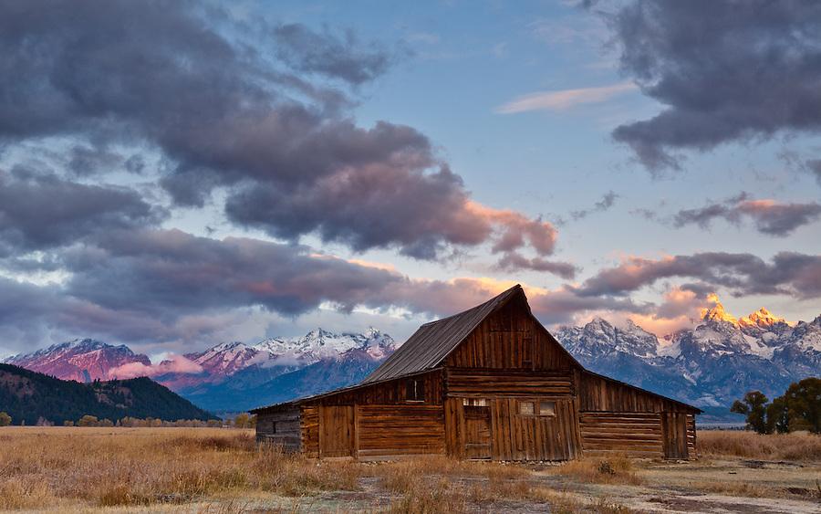Purple and orange light fills the clouds and illuminates the Teton mountains during sunrise.