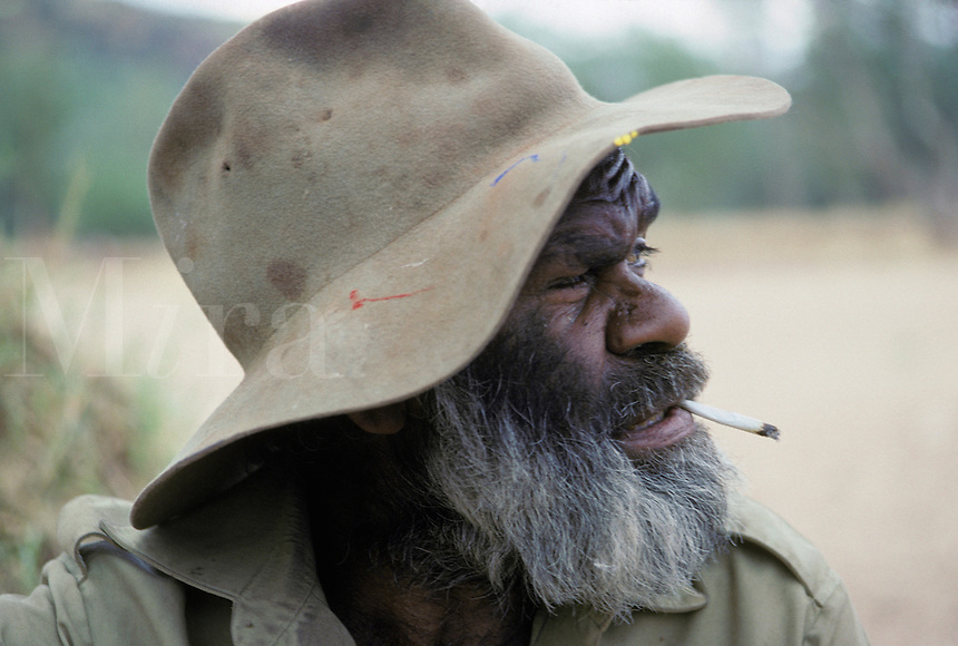 Portrait of an old man: an Australian aborigine man smoking a hand-rolled cigarette in the outback near Alice Springs, Australia.  Restrictions: no tobacc