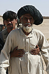 An Afghan police officer searches an old man before a meeting with NATO soldiers in the village of Osman Kheyl, in Maiwand district, Kandahar province, Afghanistan. Aug. 7, 2008. DREW BROWN/STARS AND STRIPES