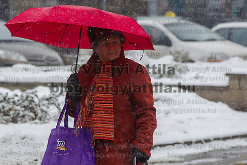 Pedestrian walks with a red umbrella in the winter snowfall in Budapest, Hungary on February 17, 2012. ATTILA VOLGYI