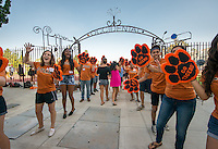The O-Team welcomes incoming first-years and their families as they walk under the art gate at the entrance to Kemp Stadium during Occidental College Orientation, Aug. 23, 2014. (Photo by Marc Campos, Occidental College Photographer)